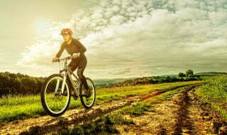 Sport bike woman on a meadow with a beautiful landscape